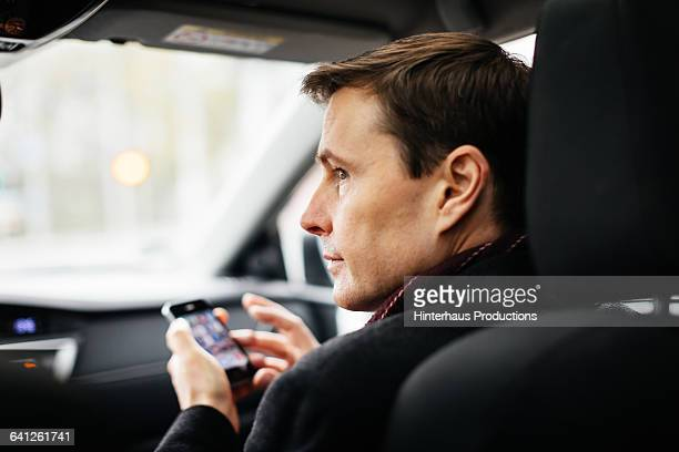 mature businessman with smart phone in a taxi - táxi - fotografias e filmes do acervo