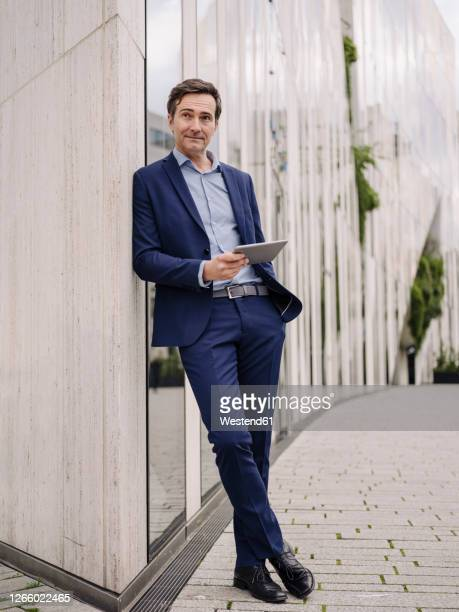 mature businessman with tablet leaning against a building in the city - businesswear stock pictures, royalty-free photos & images