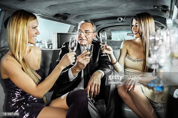Mature Homme d'affaires avec les jeunes filles dans une limousine.
