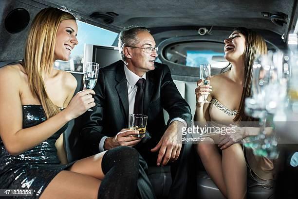 Reifer Geschäftsmann mit jungen Mädchen in einer limousine.