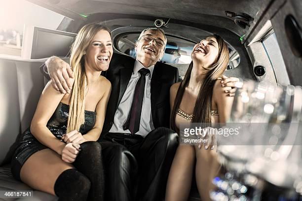 Reifer Geschäftsmann mit Junge Frauen in einer limousine.