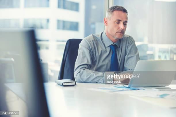 Empresario maduro trabajando en una computadora portátil.