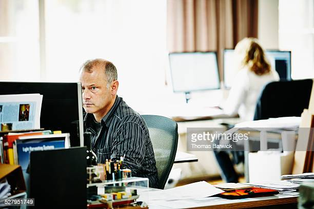 Mature businessman working on project on computer
