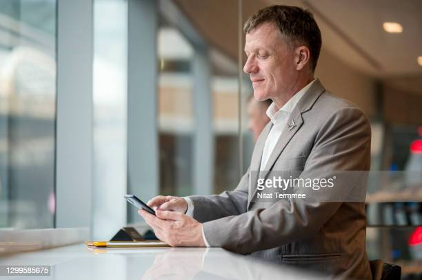 mature businessman working or text messaging through smart phone in hotel lobby. work is from anywhere at anytime concepts. - chief executive officer stock pictures, royalty-free photos & images