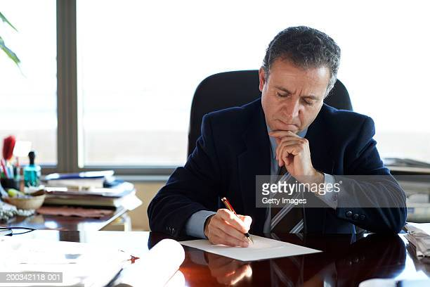 Mature businessman writing at desk