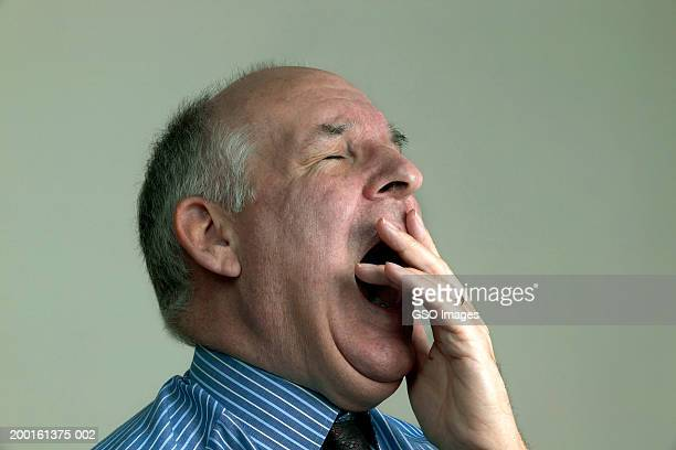 mature businessman yawning, eyes closed, close-up - あくび ストックフォトと画像