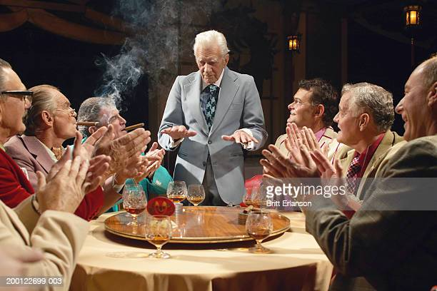 mature businessmen at table, one standing gesturing with hands - mafia foto e immagini stock