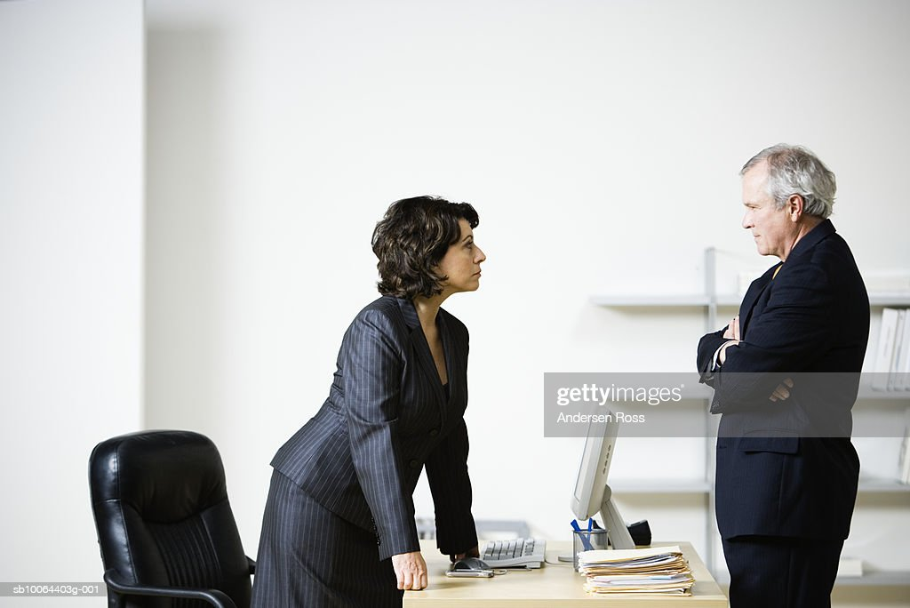 Mature businesswoman and businessman talking at desk : Stock Photo