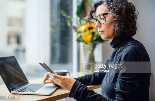 mature businesswoman at cafe - telefoon gebruiken stockfoto's en -beelden