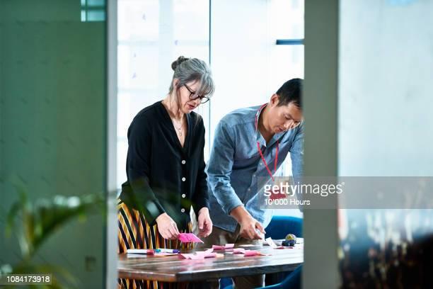 mature businesswoman brainstorming with male freelancer - thinking outside the box englische redewendung stock-fotos und bilder