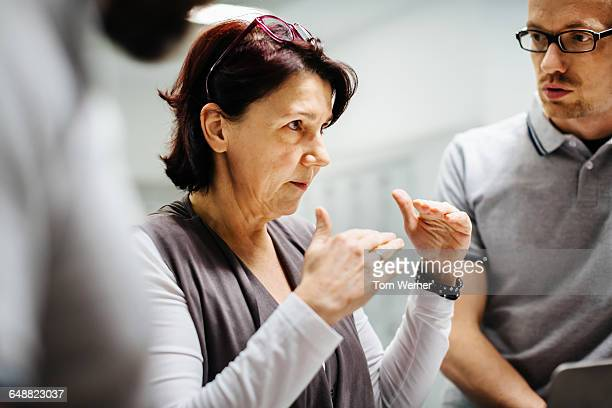 mature businesswoman briefing staff - leanincollection stock pictures, royalty-free photos & images