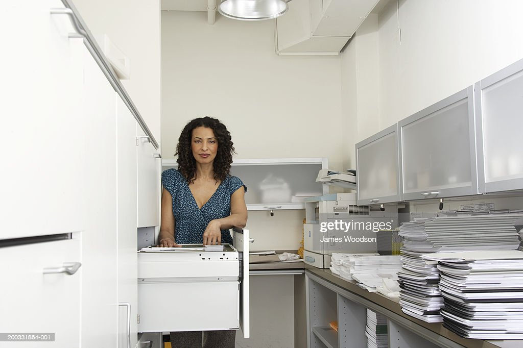 Mature businesswoman by filing cabinet in office, portrait : Stock Photo