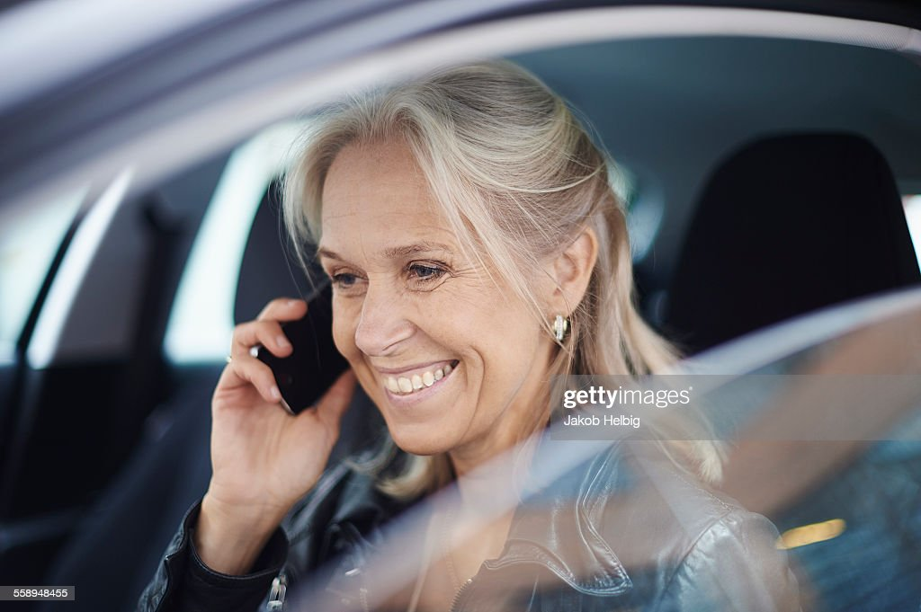 Mature businesswoman chatting on smartphone in car : Stock Photo