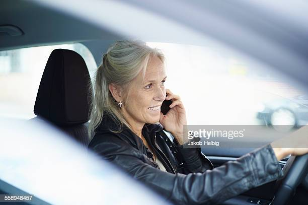Mature businesswoman chatting on smartphone whilst driving car