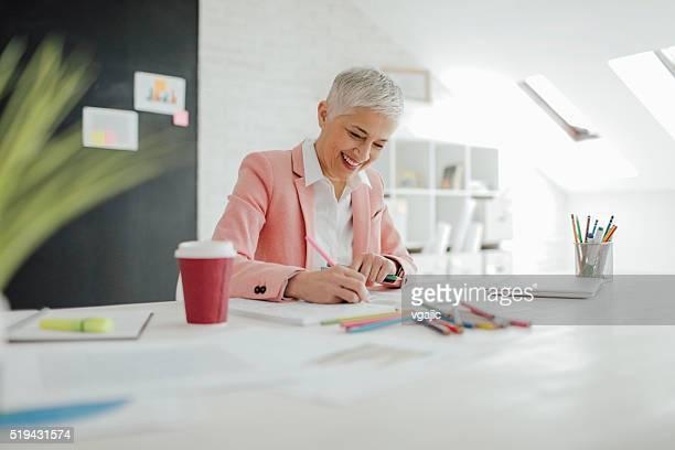 Empresaria madura para colorear libro en su oficina.