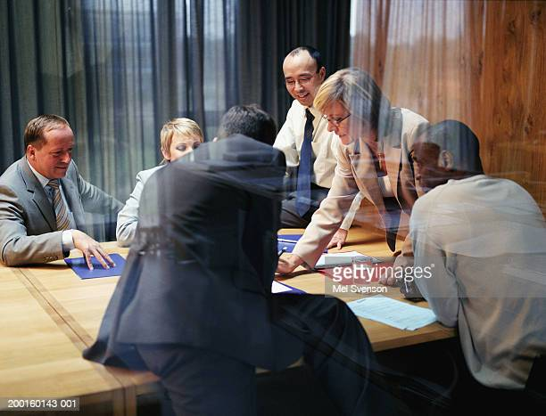Mature businesswoman conducting meeting, view through window