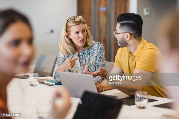 mature businesswoman discussing with colleague using laptop - gender identity stock pictures, royalty-free photos & images