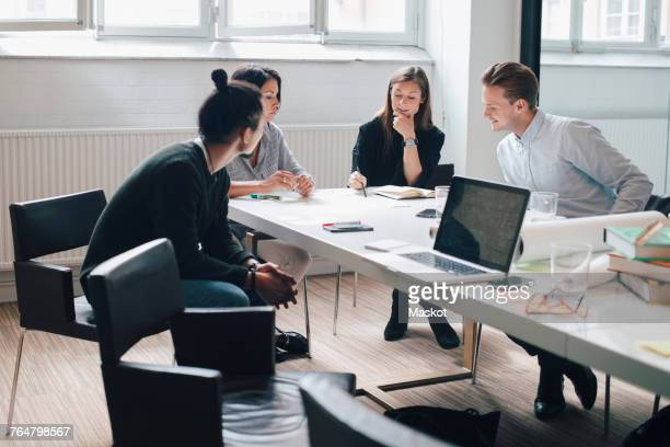 Mature businesswoman discussing with young colleagues at conference table in board room during meeting