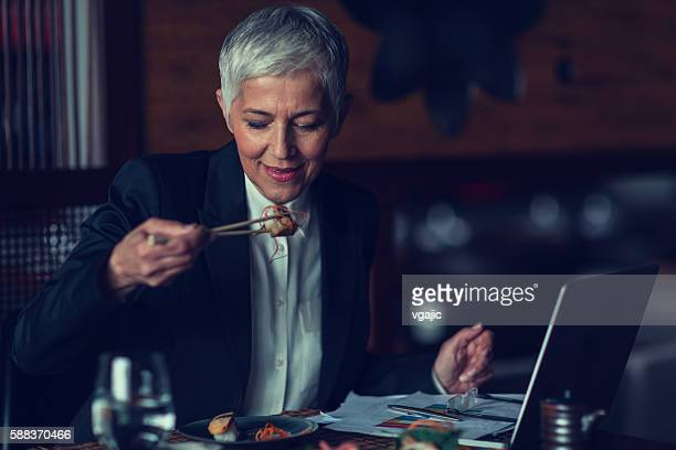 Mature Businesswoman Eating In A Restaurant And Working.