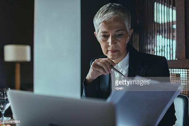 Mature Businesswoman Examining Documents.