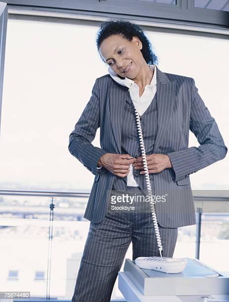 Mature businesswoman getting dressed and using landline phone