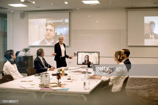 mature businesswoman giving presentation to colleagues in board room during global conference meeting at office - employee engagement stock pictures, royalty-free photos & images