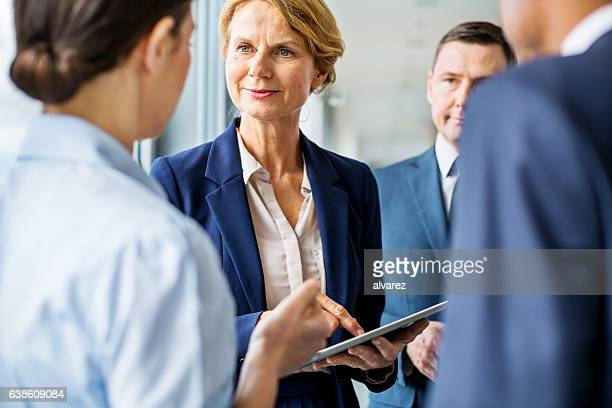 Mature businesswoman having a discussion with colleagues