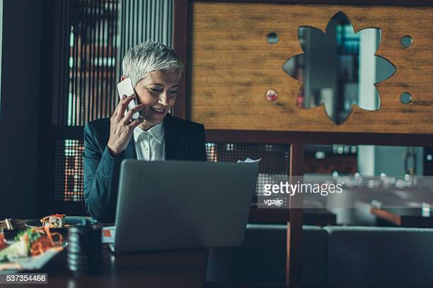 Mature Businesswoman Having Lunch And Talking On The Phone.