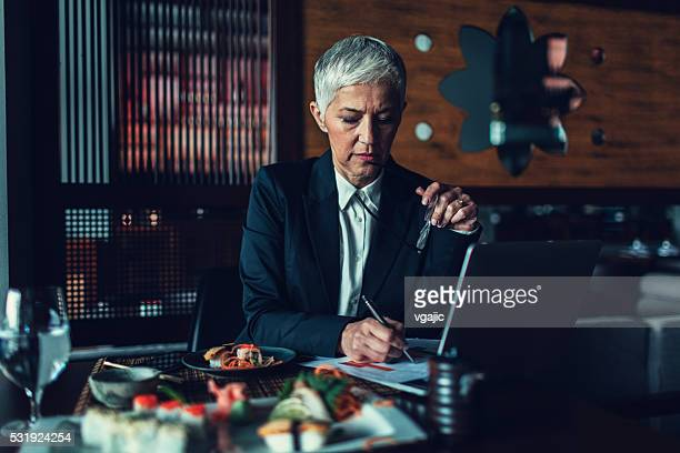Mature Businesswoman Having Working Lunch