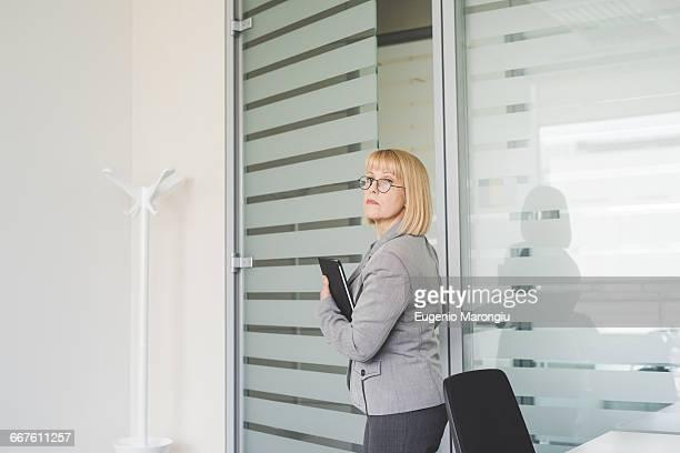 Mature businesswoman holding digital tablet leaving office