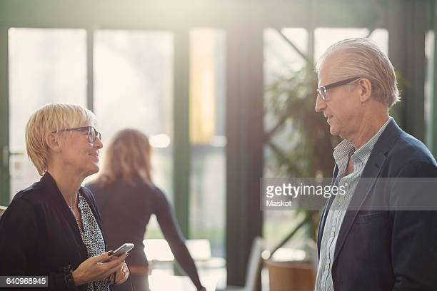 Mature businesswoman holding mobile phone while talking with colleague in office