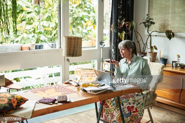 mature businesswoman holding smartphone in front of laptop at home - working seniors stock pictures, royalty-free photos & images
