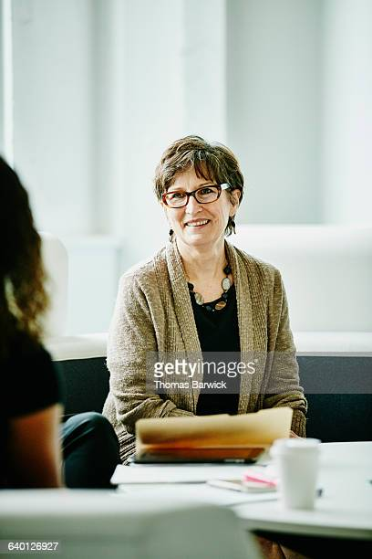 Mature businesswoman in discussion with colleagues