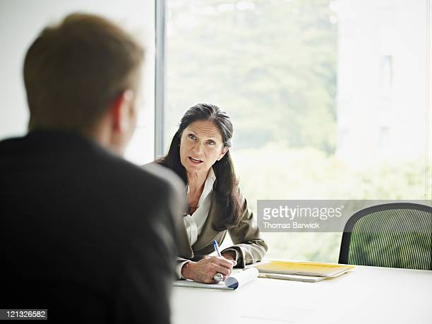mature businesswoman in discussion with coworker - leanintogether stock pictures, royalty-free photos & images