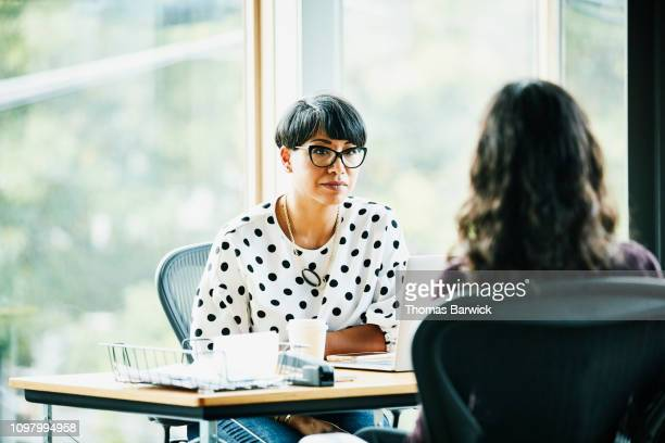 mature businesswoman in discussion with employee while seated at workstation in office - due persone foto e immagini stock