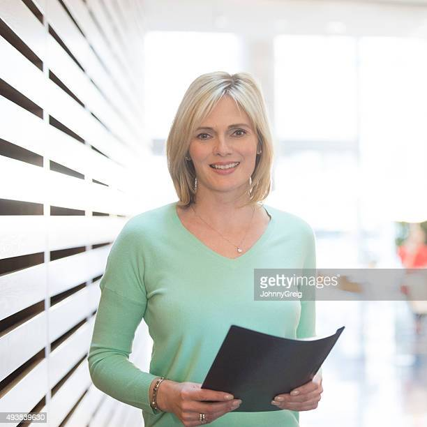 Mature businesswoman in green top holding document, portrait