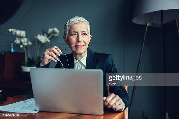 mature businesswoman in her office. - 短毛 個照片及圖片檔