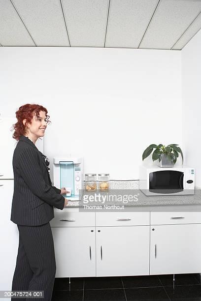 Mature businesswoman in office kitchen, side view
