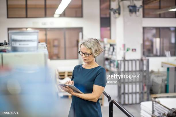 Mature businesswoman in printing press using digital tablet