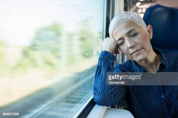 mature businesswoman in train - passenger train stock photos and pictures