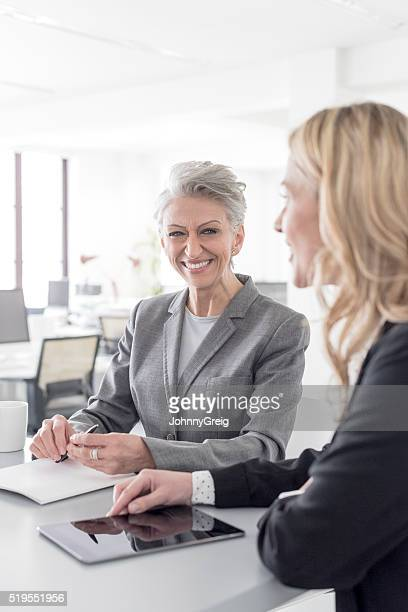 Mature businesswoman laughing with mid adult office worker