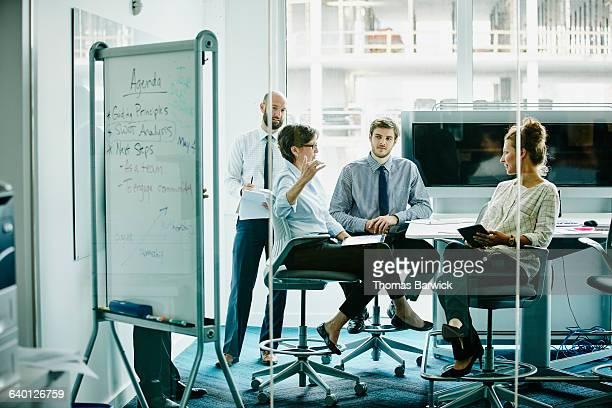 mature businesswoman leading meeting in office - business finance and industry stock pictures, royalty-free photos & images