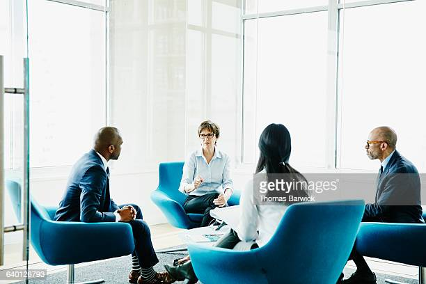 mature businesswoman leading meeting in office - finanzen und wirtschaft stock-fotos und bilder