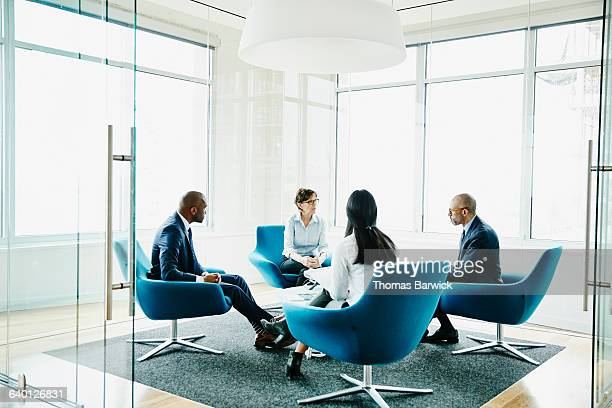 mature businesswoman leading meeting in office - vier personen stock-fotos und bilder