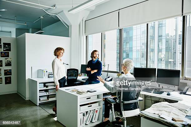 mature businesswoman leading meeting in office - leanintogether stock pictures, royalty-free photos & images
