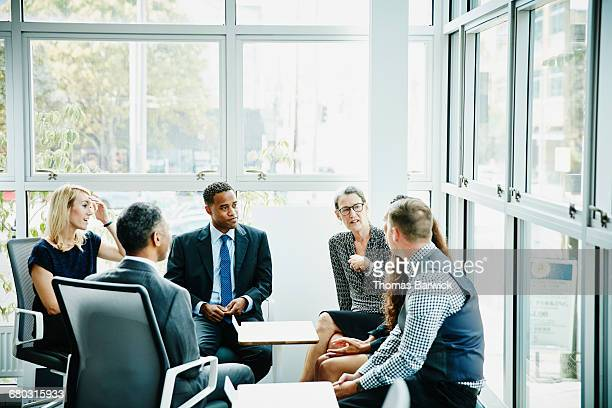mature businesswoman leading team meeting - leanintogether stock pictures, royalty-free photos & images