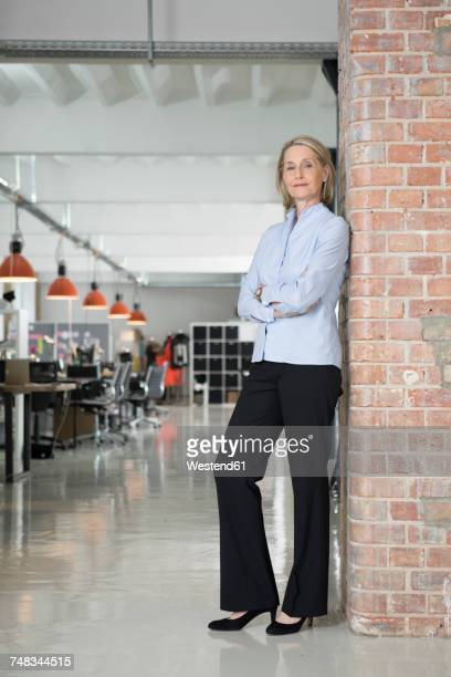 Mature businesswoman leaning against brick wall