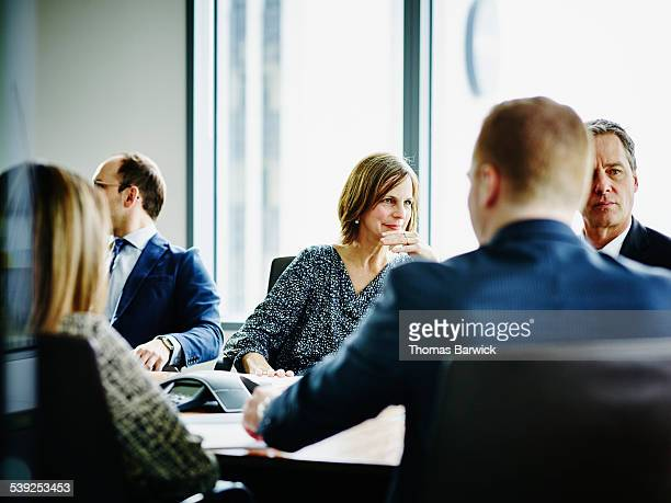 Mature businesswoman listening during meeting