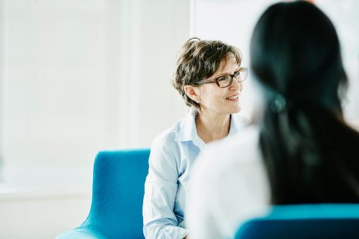 Mature businesswoman listening during meeting - gettyimageskorea