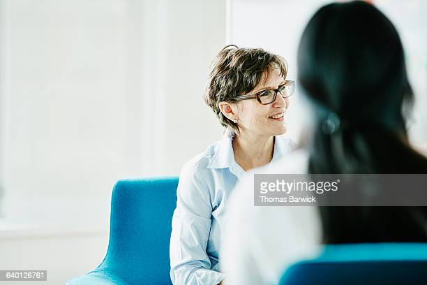 mature businesswoman listening during meeting - trust stock pictures, royalty-free photos & images